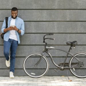 Young Black Man Using Smartphone, Standing Next To His Bike Outdoors
